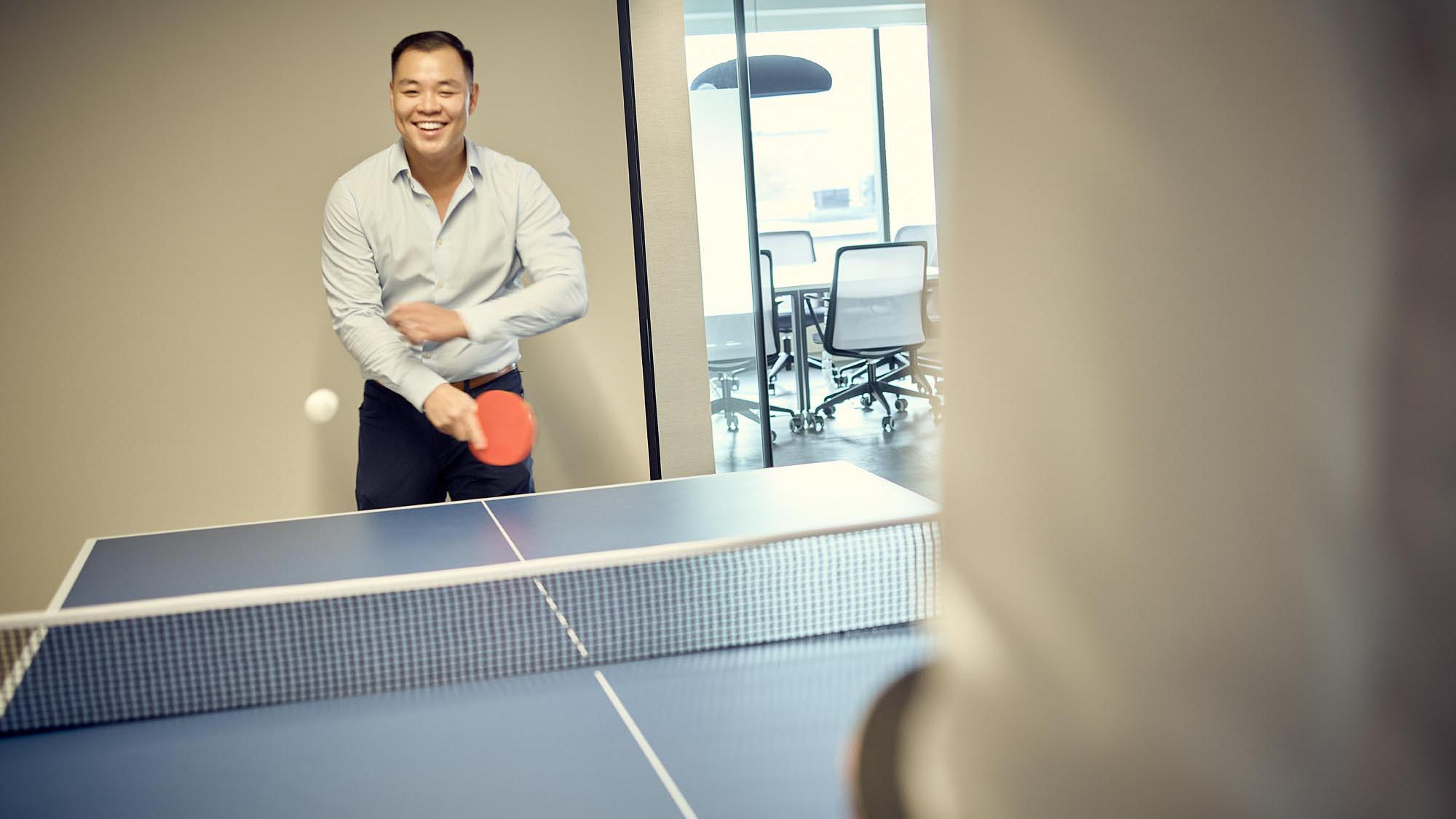 Two employees playing ping pong in an office