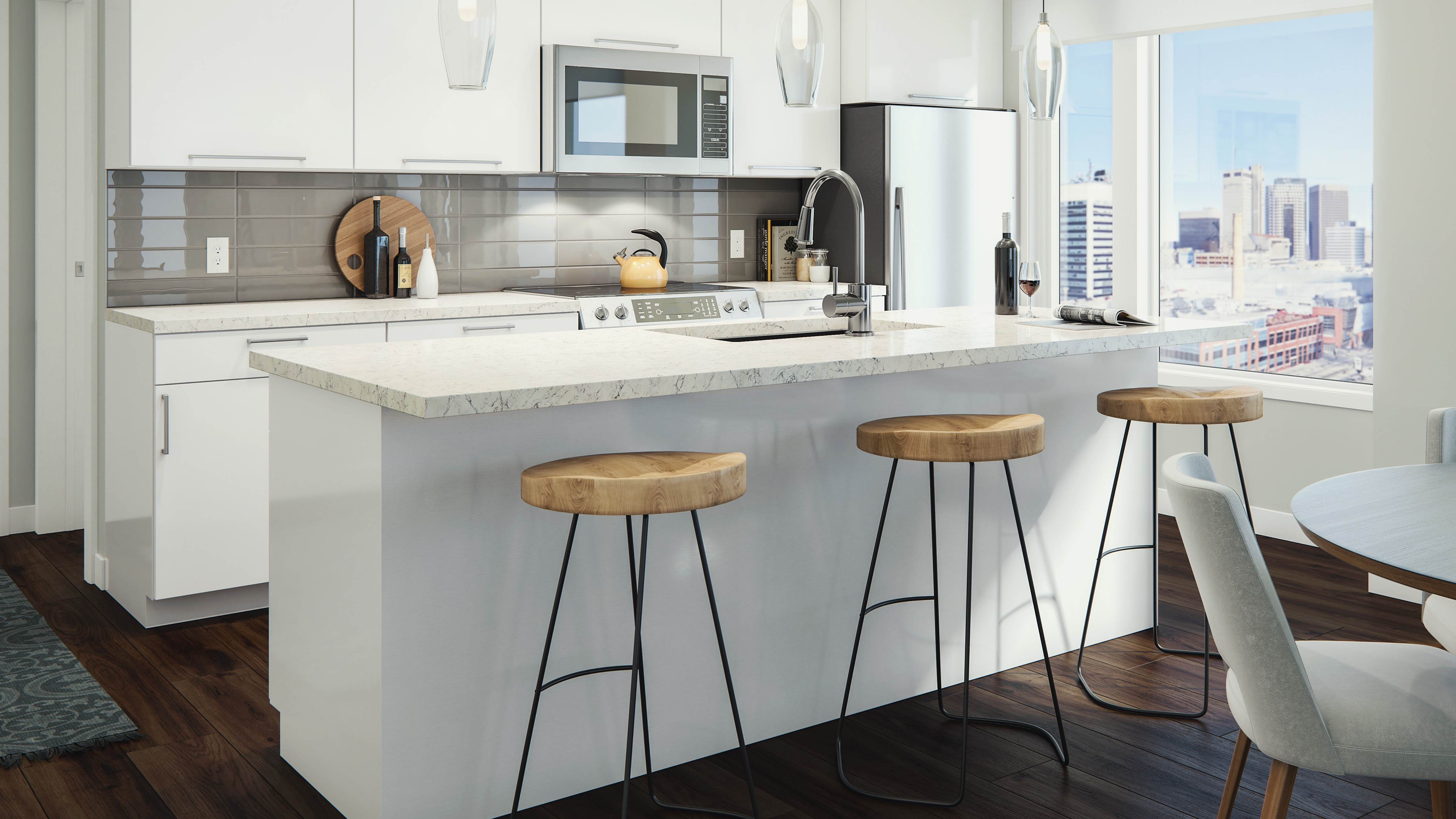 Interior of apartment suite's kitchen with island built in appliances and bar stools